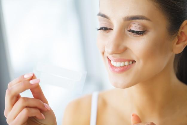 Wybielanie zębów. piękna uśmiechnięta kobieta trzyma pasek wybielający. Premium Zdjęcia