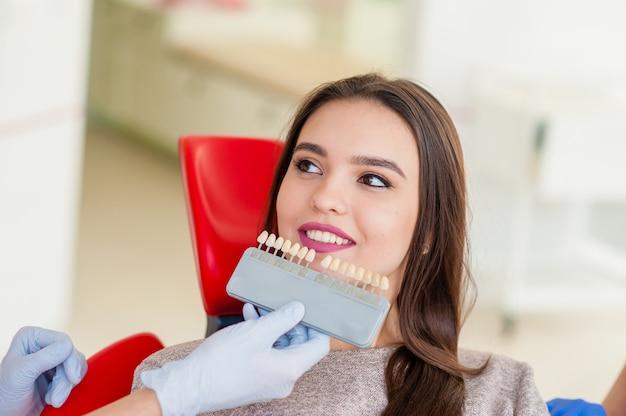 Wybór koloru zębów dla pięknej dziewczyny w stomatologii. Premium Zdjęcia