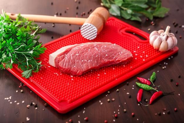 Wybór surowego mięsa na drewnianą deską do krojenia Premium Zdjęcia