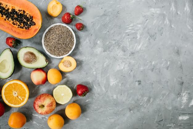 Wybór Zdrowej żywności: Owoce, Jagody, Nasiona Chia, Superfood Na Szarym Tle Betonu. Widok Z Góry, Leżak Płaski. Wysokiej Jakości Zdjęcie Premium Zdjęcia