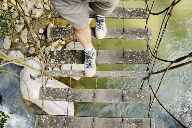Wycieczkować buty krzyżuje niebezpiecznego most drewniane deski na rzece Premium Zdjęcia