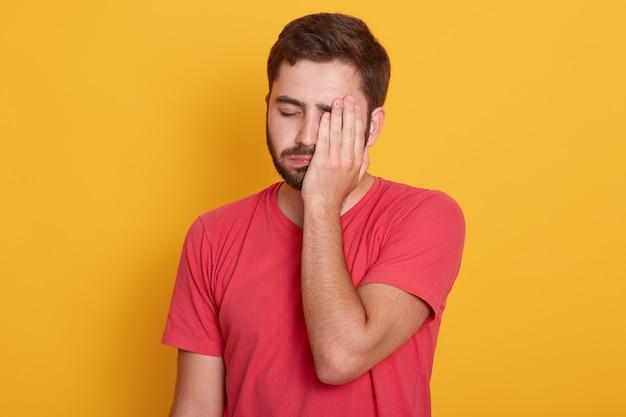 Wyczerpana Młoda Nieogolona Połowa Twarzy Z Ręką, Stojąca Przed żółtym Studio, Wygląda Na Zmęczoną I Ma Depresję Darmowe Zdjęcia