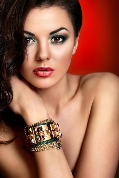 Wygląd Mody. Seksowny Portret Zbliżenie Piękny Seksowny Kaukaski Młoda Kobieta Model Z Czerwonymi Ustami, Jasny Zielony Makijaż, Z Idealnie Czystą Skórę Z Biżuterią Pod Ręką Na Białym Tle Na Czerwonym Tle Darmowe Zdjęcia