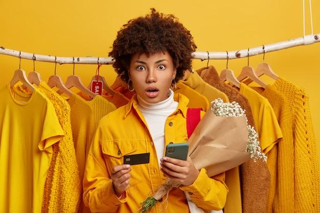 Wygodna Koncepcja Bankowości I Zakupów Online. Zdumiona Młoda Afroamerykanka Zdumiała Zszokowane Spojrzenie Na Aparat, Trzyma Telefon Komórkowy I Bukiet, żółte Ubrania Na Wieszakach W Tle Darmowe Zdjęcia