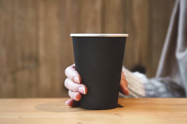 Wykonaj Papierową Filiżankę Kawy W Kobiecej Dłoni W Kawiarni Premium Zdjęcia