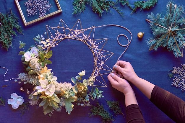 Wykonanie Dekoracyjnego Wieńca świątecznego Na Klasycznym Niebieskim Lnie. Kobiece Ręce Tworzą Ręcznie Wieniec. Dekoracje Na Boże Narodzenie. Premium Zdjęcia