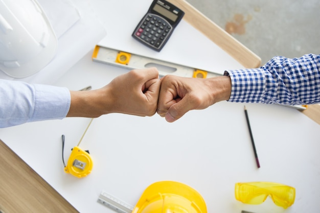 Wykonawca odniósł sukces w pracy zespołowej. inżynier i partnerzy architektoniczni dający pięść po kompletnej transakcji. Premium Zdjęcia