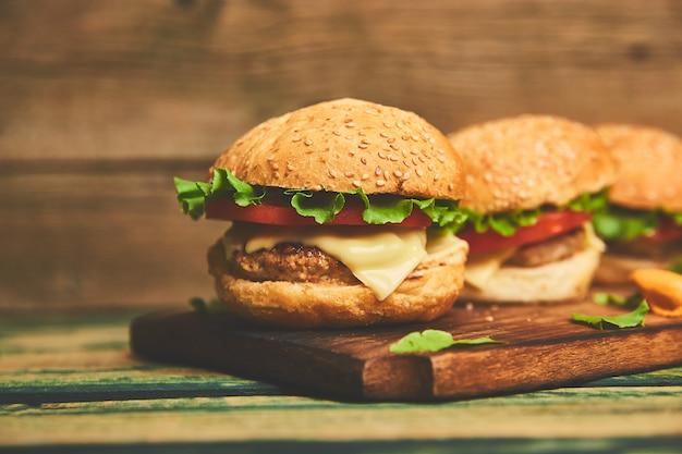Wykonuje Ręcznie Wołowina Hamburger Na Drewnianym Stole Odizolowywającym Na Czarnym Tle. Premium Zdjęcia