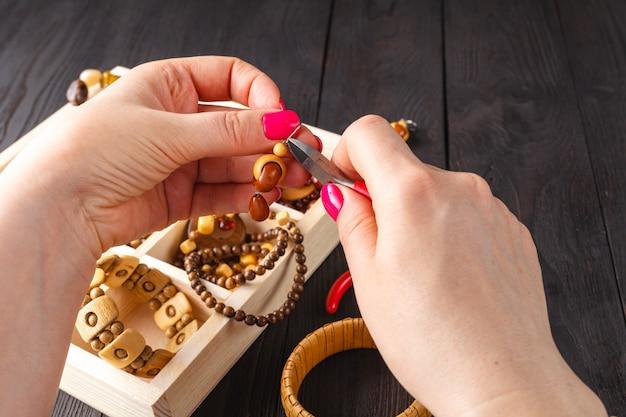 Wykonywanie Ręcznie Robionej Biżuterii. Pudełko Z Koralikami Na Starym Drewnianym Stole. Premium Zdjęcia