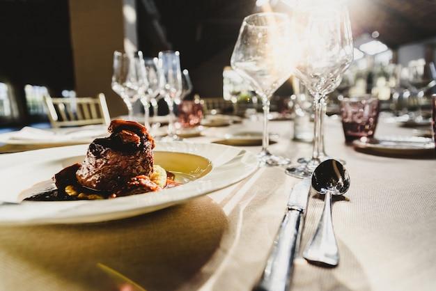 Wykwintne danie cielęce w sosie serwowane w luksusowych sztućcach z promieniami słońca w restauracji. Premium Zdjęcia