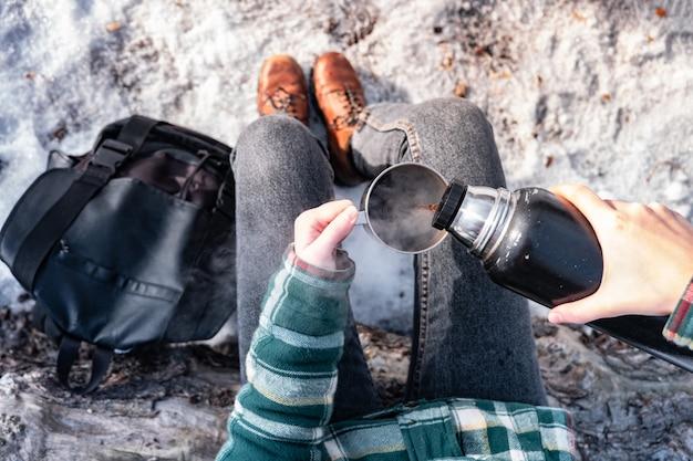 Wylewanie Gorącego Napoju Z Termosu Na Kempingu. Osoba W Zimowym Lesie Podczas Wędrówki Robi Się Ciepła, Strzał Z Punktu Widzenia Premium Zdjęcia