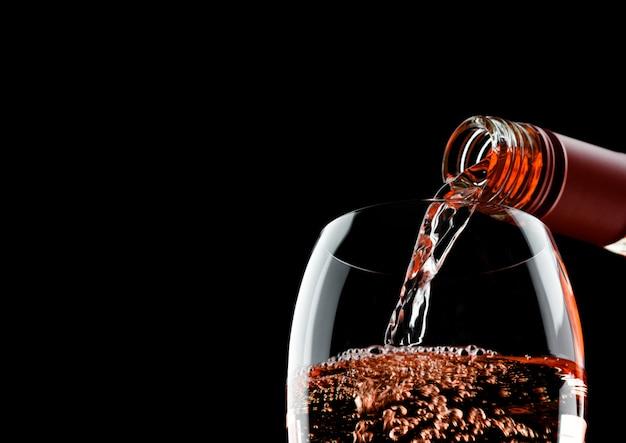 Wylewanie Różowego Wina Różowego Z Butelki Do Szklanki Na Białym Tle Premium Zdjęcia