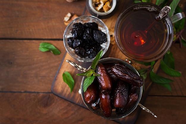 Wymieszaj Suszone Owoce (owoce Palmy Daktylowej, Suszone śliwki, Suszone Morele, Rodzynki) I Orzechy Oraz Tradycyjną Arabską Herbatę. Jedzenie Ramadan (ramazan). Widok Z Góry Premium Zdjęcia