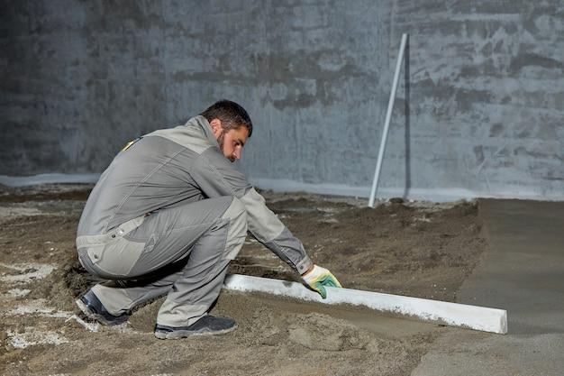 Wypełnienie Podłogi Betonem, Wylewką Oraz Wyrównanie Podłogi Przez Pracowników Budowlanych. Gładkie Podłogi Wykonane Z Mieszanki Cementu Premium Zdjęcia