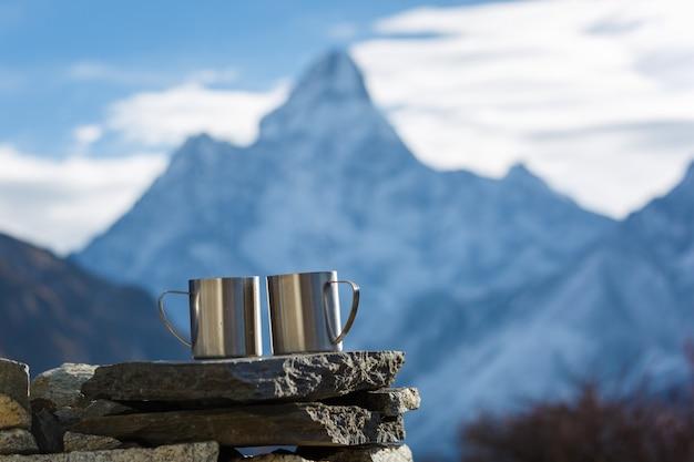 Wyprawa Do Everest Base Camp. Dwie Filiżanki Herbaty Na Tle Góry Ama Dablam W Centrum Uwagi. Tło Góry Niewyraźne. Premium Zdjęcia