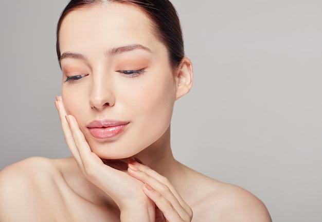Wyrafinowana dziewczyna z pełnymi ustami, ciemnymi włosami i promiennie czystą delikatną skórą na szarym. pani dotyka twarzy dłonią. patrząc z boku. pielęgnacja skóry, kosmetologia. wellness. Premium Zdjęcia