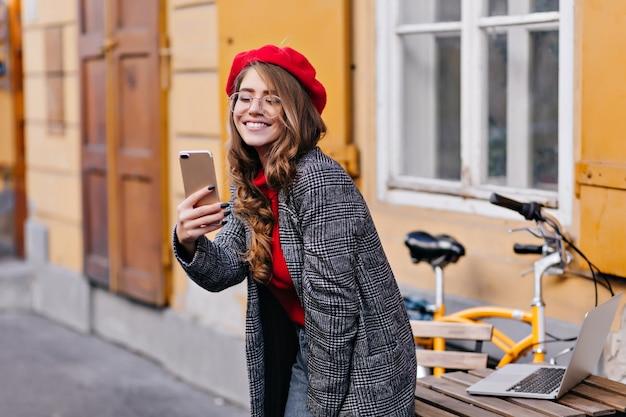 Wyrafinowana Francuska Kręcona Dziewczyna Robi Selfie W Pobliżu Drewnianego Stołu Z Laptopem Na Nim Darmowe Zdjęcia