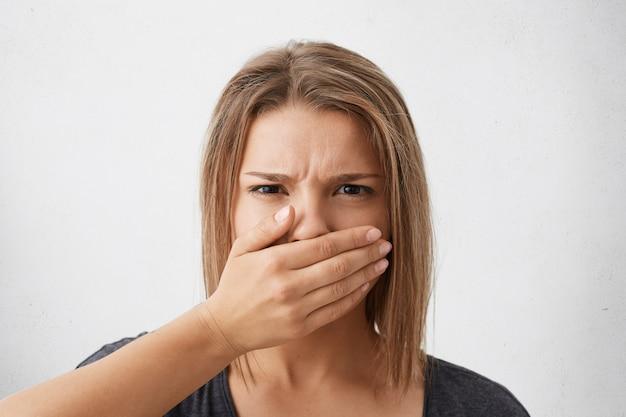 Wyraz Twarzy I Emocje Człowieka. Zdjęcie W Głowę Wystraszonej Młodej Kobiety Z Fryzurą Bob Zakrywającą Usta Dłonią, Jakby Nie Wolno Było Nic Mówić, Patrząc Oczami Pełnymi Przerażenia Darmowe Zdjęcia