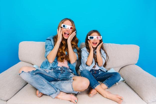 Wyrażając Szalone Szczęśliwe Prawdziwe Emocje Do Kamery Modnej Matki I Jej Córki W Dżinsach Na Kanapie Na Białym Tle Na Niebieskim Tle. Noszenie Okularów 3d, Wspólna Zabawa Darmowe Zdjęcia