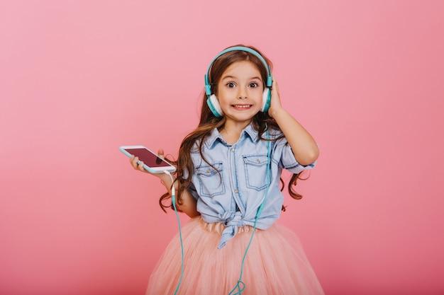 Wyrażanie Pozytywności Szczęśliwego Dziecka Słuchającego Muzyki Przez Niebieskie Słuchawki Na Białym Tle Na Różowym Tle. Całkiem Mała Dziewczynka Z Długimi Włosami Brunetka Uśmiecha Się Do Kamery W Tiulowej Spódnicy Darmowe Zdjęcia