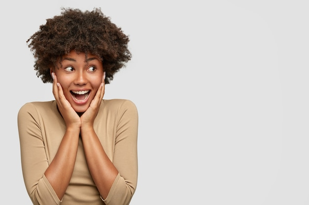 Wyrazista Atrakcyjna Afroamerykanka Wykrzykuje Ze Szczęścia, Trzyma Dłonie Na Policzkach, Radośnie Patrzy Na Bok, Gdy Zauważa Wracającą Z Zagranicy Najlepszą Przyjaciółkę, Stoi Pod Białą ścianą, Puste Miejsce Darmowe Zdjęcia