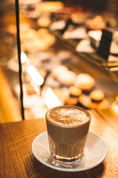 Wyśmienicie latte filiżanka z tłem defocus piekarni rzecz Darmowe Zdjęcia