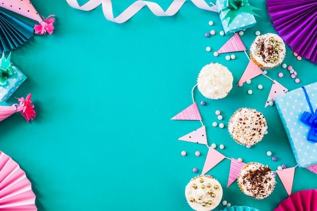 Wyśmienicie Muffins Z Partyjnymi Akcesoriami Na Zieleni Powierzchni Darmowe Zdjęcia
