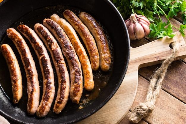 Wyśmienicie Smażone Kiełbasy Z Złotą Skorupą W żelaznej Obsadzie Patelni, świeży Pietruszka Czosnek Na Drewno Stole Premium Zdjęcia