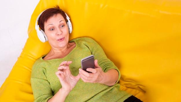 Wysoka kobieta starszy kąt leżał słuchania muzyki Darmowe Zdjęcia