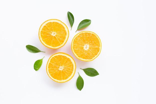 Wysoka witamina c. świeży pomarańczowy owoc cytrusowy z liśćmi odizolowywającymi na biel powierzchni. Premium Zdjęcia