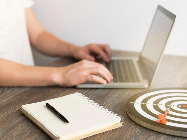 Wysoki Kąt Człowieka Pracującego Na Laptopie Z Rzutką I Wyżywienie Obok Niego Darmowe Zdjęcia