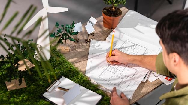 Wysoki Kąt Człowieka Pracującego Nad Projektem Ekologicznej Energii Wiatrowej Z Papierowymi Planami Darmowe Zdjęcia