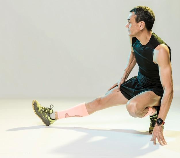 Wysoki Kąt Człowieka Rozciąganie Przed ćwiczeniami Darmowe Zdjęcia