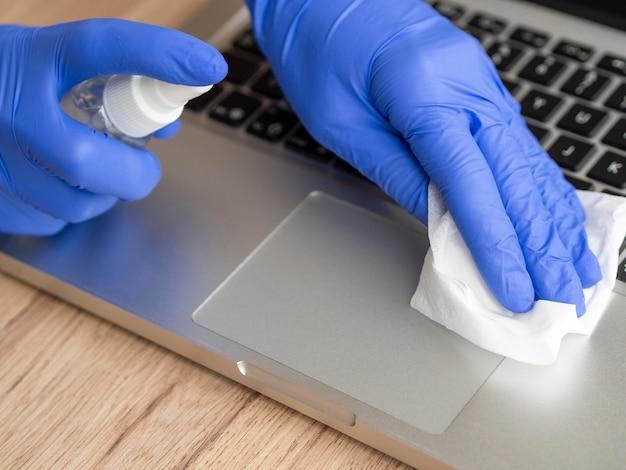 Wysoki Kąt Dłoni W Rękawiczkach Chirurgicznych Dezynfekujących Powierzchnię Laptopa Darmowe Zdjęcia