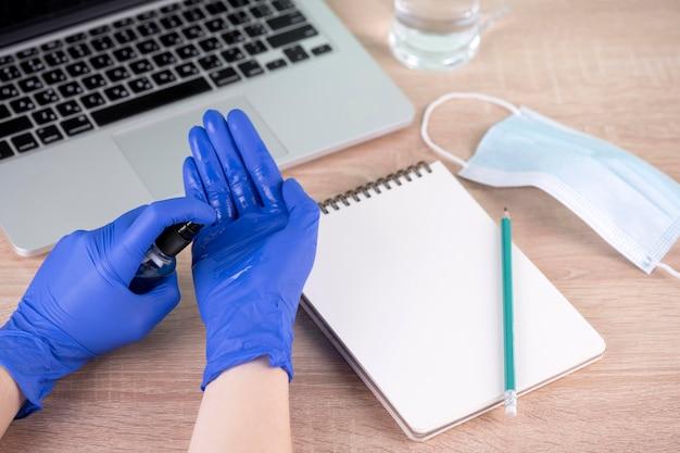 Wysoki Kąt Dłoni Z Rękawiczkami Chirurgicznymi I środkiem Odkażającym Do Rąk Obok Biurka Darmowe Zdjęcia