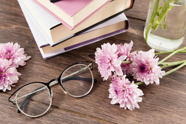 Wysoki Kąt Książek Kwiaty I Szkła Na Drewnianym Stole Darmowe Zdjęcia