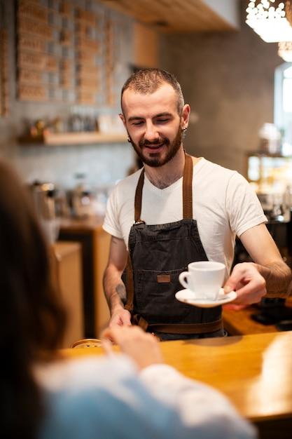 Wysoki kąt mężczyzna barista serwująca kawę Darmowe Zdjęcia