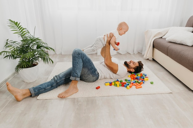 Wysoki Kąt Ojca Bawiącego Się Na Podłodze Z Dzieckiem Darmowe Zdjęcia