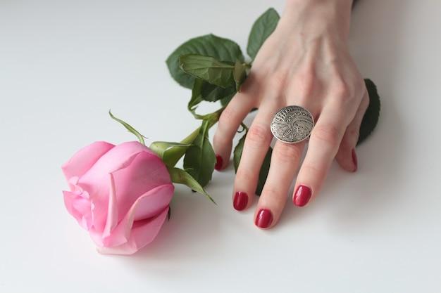 Wysoki Kąt Strzał Kobiecej Dłoni Z Pięknym Srebrnym Pierścieniem Na Róży Z Zielonymi Liśćmi Darmowe Zdjęcia