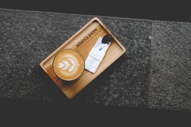 Wysoki Kąt Strzału Filiżankę Sztuki Latte Na Drewnianej Tacy Darmowe Zdjęcia