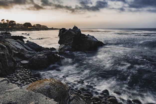 Wysoki Kąt Strzału Małych Skał Na Brzegu Morza Pod Zachmurzonym Niebem Wieczorem Darmowe Zdjęcia