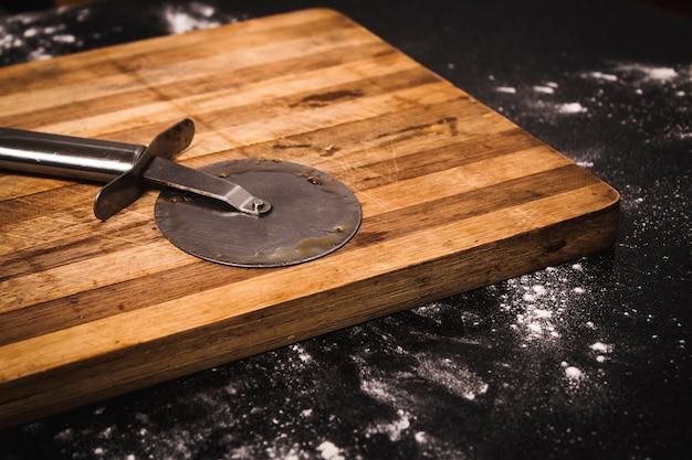 Wysoki Kąt Strzału Nożem Do Pizzy Na Drewnianą Deską Do Krojenia Na Czarnej Powierzchni Premium Zdjęcia