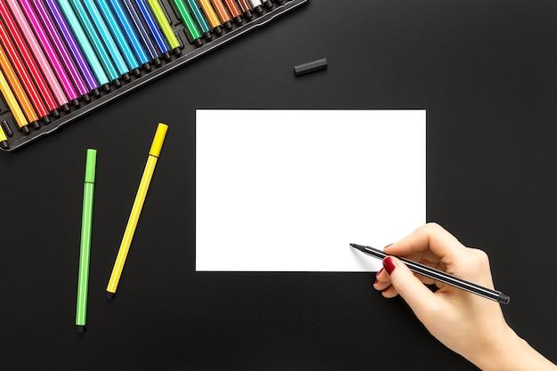 Wysoki Kąt Strzału Osoby Rysującej Na Białym Papierze Z Kolorowymi Piórami Na Czarnej Powierzchni Darmowe Zdjęcia