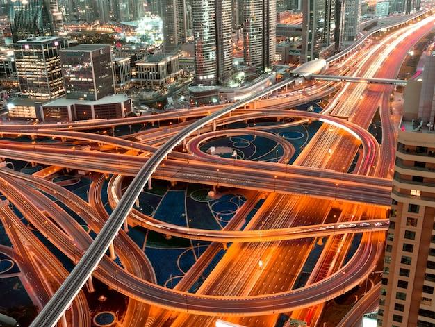 Wysoki Kąt Strzału Oświetlonej Autostrady Z Wielopoziomowymi Skrzyżowaniami W Megapolis W Nocy Darmowe Zdjęcia