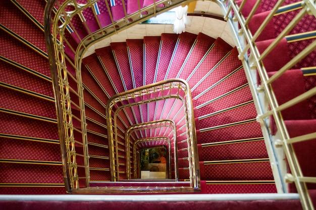 Wysoki Kąt Strzału Różowy Spiralne Schody Ze Złotymi Uchwytami W Pięknym Budynku Darmowe Zdjęcia