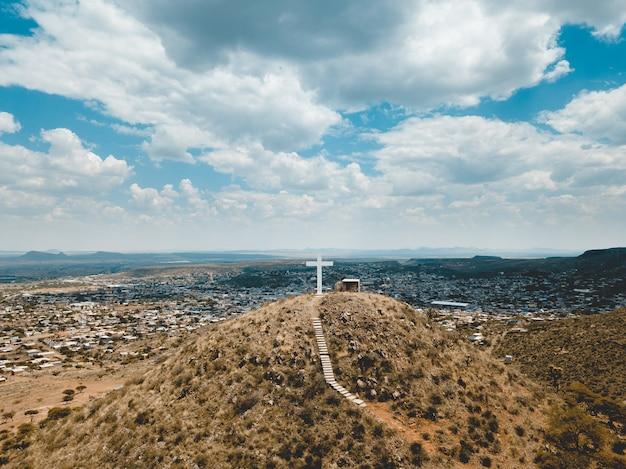 Wysoki Kąt Strzału Wzgórz Pokrytych Suchą Trawą Z Dużym Białym Krzyżem Na Szczycie Pod Błękitnym Niebem Darmowe Zdjęcia