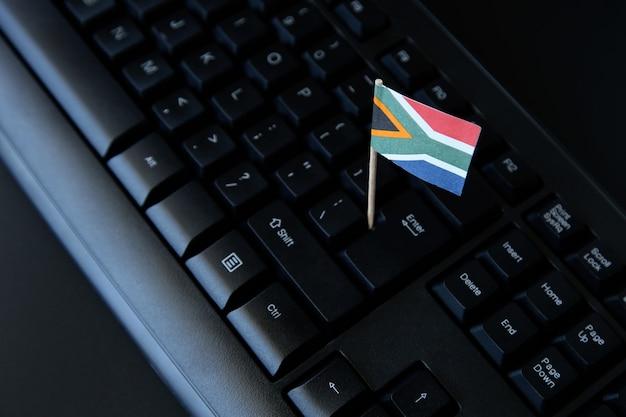 Wysoki Kąt Strzału Z Małą Flagą Republiki Południowej Afryki Na Czarnej Klawiaturze Komputera Darmowe Zdjęcia
