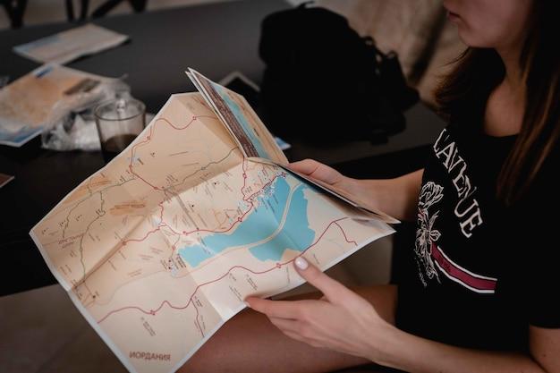 Wysoki Kąt Ujęcie Kobiety Trzymającej Mapę I Czytającej Ją W Celu Znalezienia Drogi Darmowe Zdjęcia