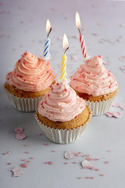 Wysoki Kąt Urodzinowych Babeczek Z Polewą I Zapalonymi świecami Darmowe Zdjęcia