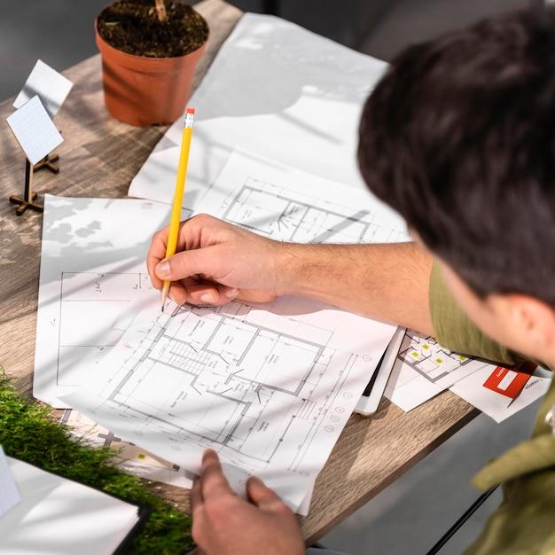 Wysoki Kąt Widzenia Człowieka Pracującego Nad Projektem Ekologicznej Energii Wiatrowej Z Papierami I Ołówkiem Darmowe Zdjęcia